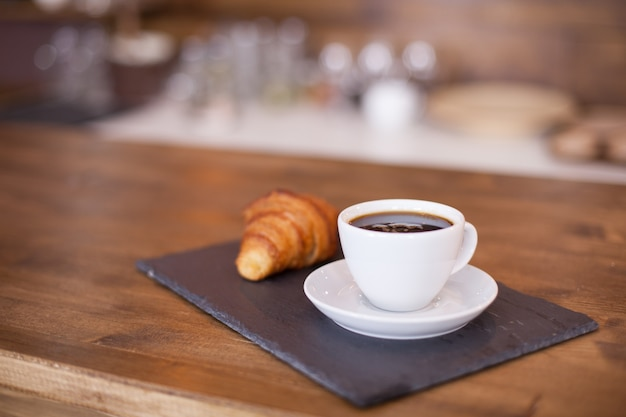 Black coffee served with pastry waiting for the client. parisian dessert. wooden bar counter.