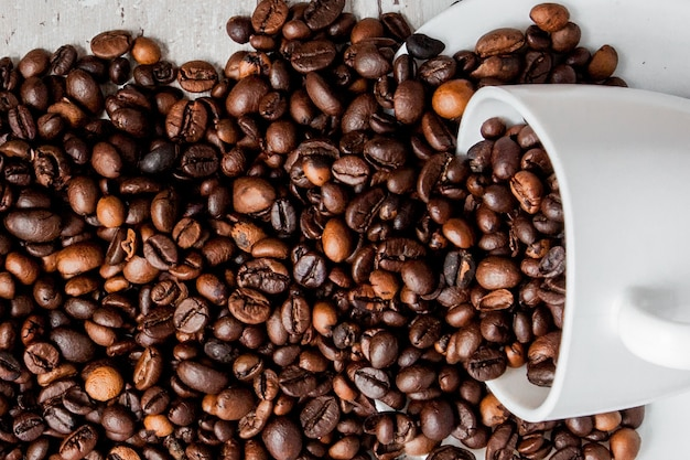 Black coffee in white cup and coffee beans on light wooden background. top view, space for text.