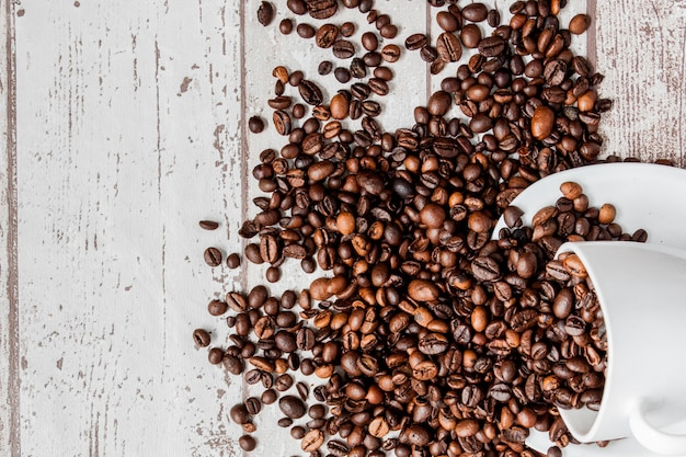 Black coffee in white cup and coffee beans on light wooden background.