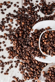 Black coffee in white cup and coffee beans on light wooden