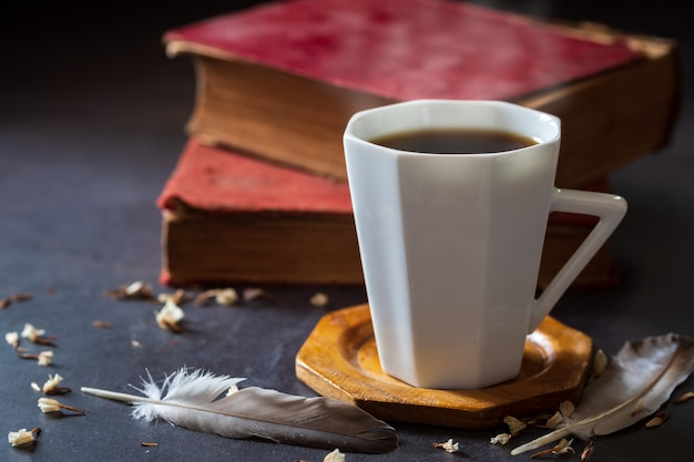 Black coffee in white cup and old books with feather and dried flower petals placed on the marble table and morning sunlight.