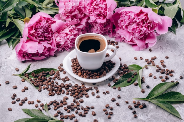 Black coffee in a white cup and pink-colored peonies
