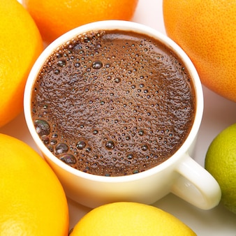 Black coffee in a white cup surrounded by citrus fruits