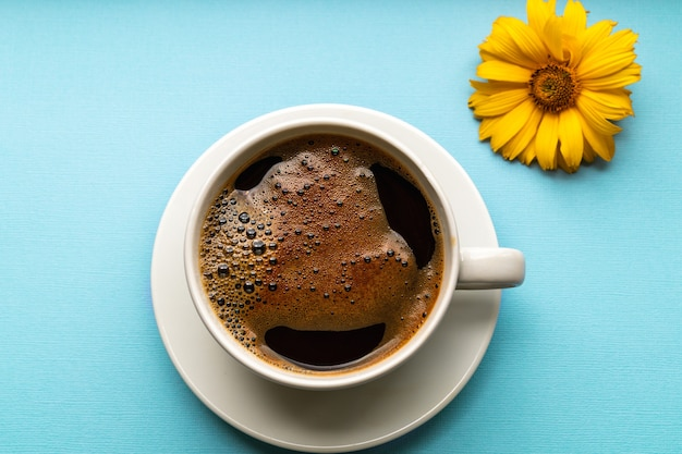 Черный кофе с пеной в белой чашке на синем фоне, плоская планировка.