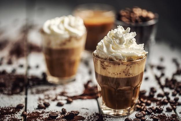 Черный кофе со взбитыми сливками в стеклянных чашках и пролитыми кофейными зернами.