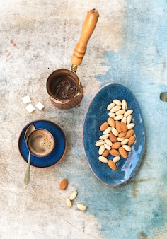 Black coffeee with almonds and pistachios over light blue table. top view