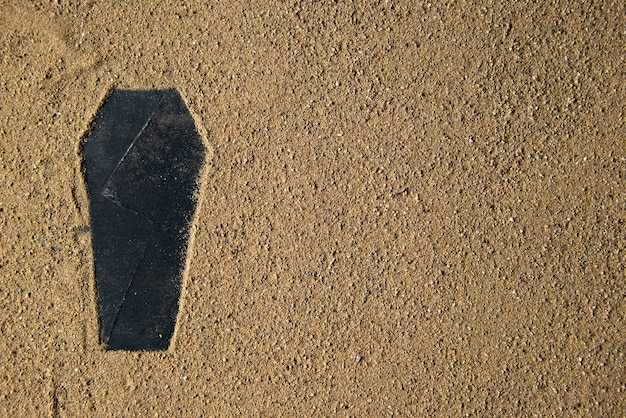 Black coffin shape made on the sand