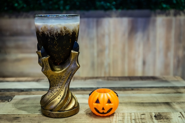 Black cola drink in a magic fantasy glass with a pumpkin, halloween night party