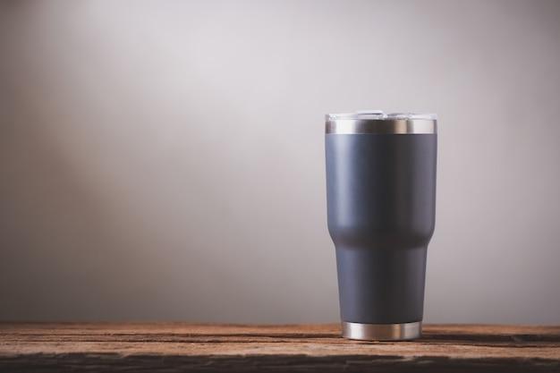 木製のテーブルの上の黒い冷たいカップ