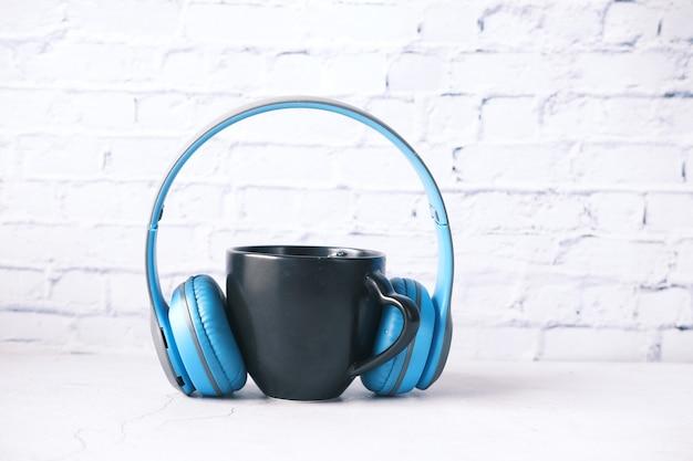 Кофейная кружка черного цвета и головной телефон на столе