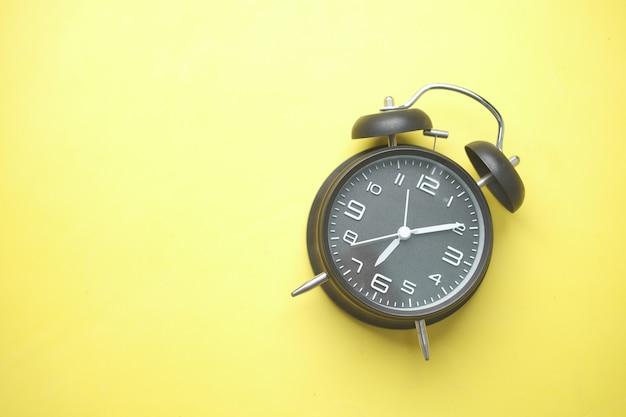 노란색에 검은 색 오래 된 알람 시계