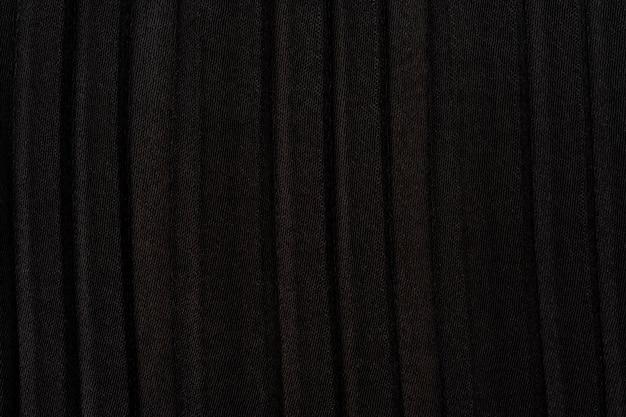 黒い色のプリーツ生地の背景のテクスチャ。背景のマクロビューテクスチャ、プリーツテクスチャ