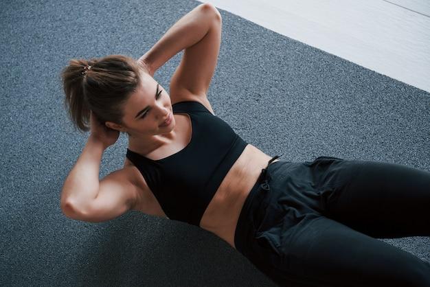 In vestiti di colore nero. fare gli addominali sul pavimento in palestra. bella donna fitness femminile