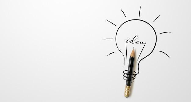 Черный цветной карандаш с контурным рисунком лампочки и словом идея на белом фоне