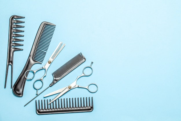 Black combs and combs with scissors on blue background. copy space for text.