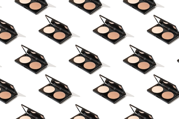 Черная компактная палитра с тональным кремом, пудрой, бронзером, открытая зеркалом. нанесение тонального макияжа для профессионального визажиста. яркий узор косметических товаров на белом фоне.
