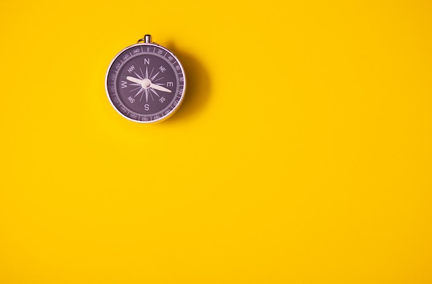 Black compass on yellow background, equipment for travel, tourism and business, top view