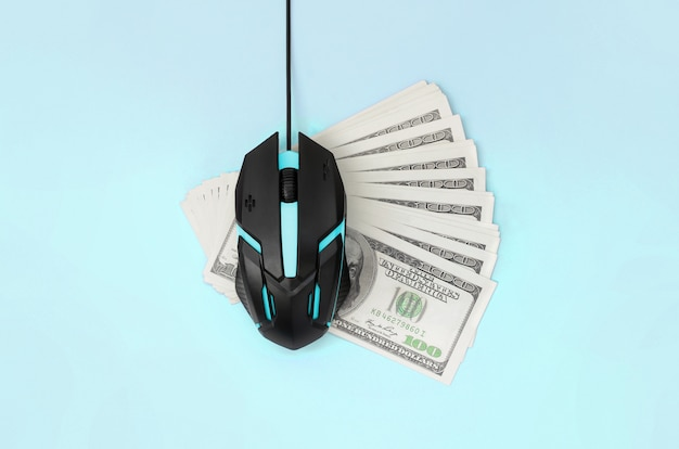 Black computer mouse on many hundred dollar bills