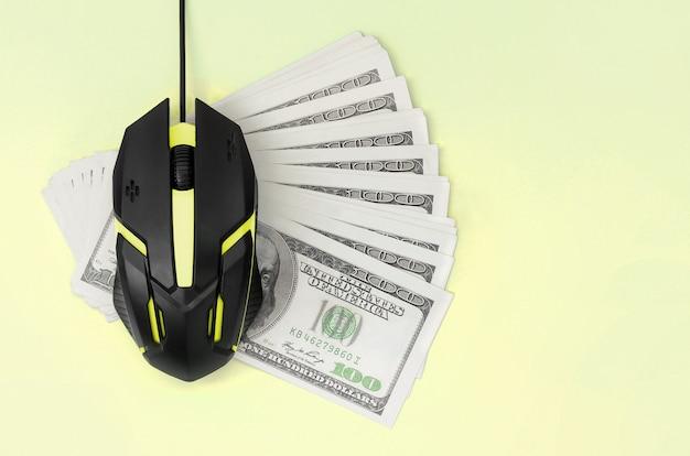 Black computer mouse on many hundred dollar bills