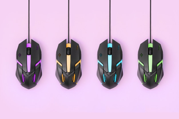 Black computer mouses hang on pastel pink background