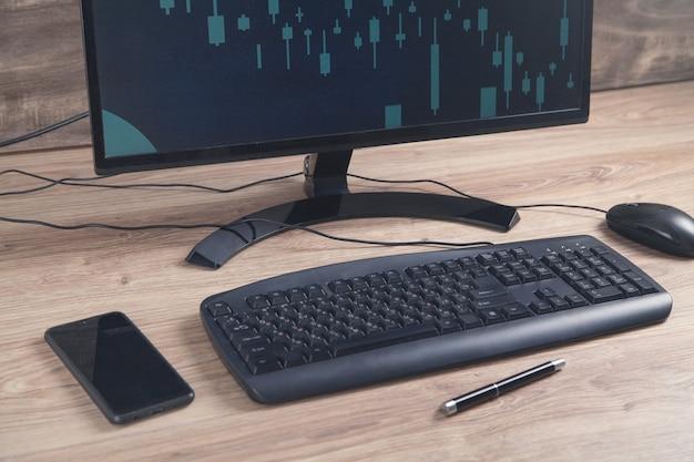 키보드와 마우스 테이블에 검은 컴퓨터. 화면에 그래프와 차트. 분석. 사업