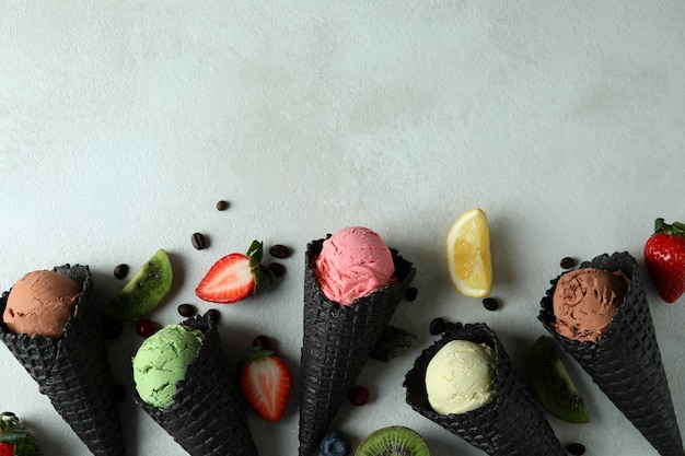 Black cones with ice cream and ingredients on white textured