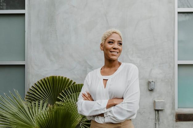 植物のそばに立っている黒人の自信のある女性