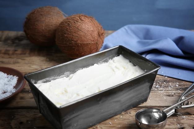 木製のテーブルに新鮮なココナッツアイスクリームが入った黒い容器