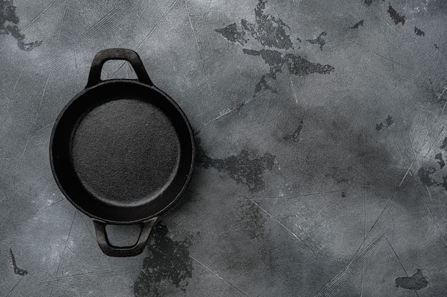 Black cooking pot set with copy space for text or food with copy space for text or food, top view flat lay, on gray stone table background