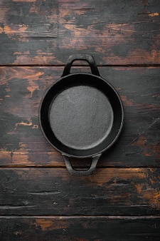 Black cooking pot set with copy space for text or food with copy space for text or food, top view flat lay, on old dark  wooden table background