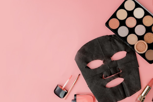 Black cosmetic mask and makeup set on pink background with copy space