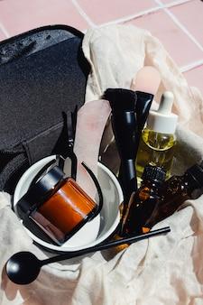トラベルサイズのミニチュア美容フェイシャル製品のセットが付いた黒い化粧品必要なバッグ