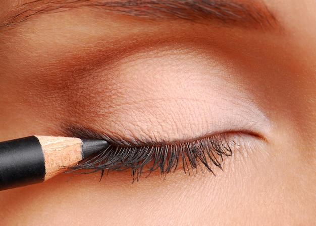 Черный косметический карандаш. глаза женщины закрыты. длинные ресницы.