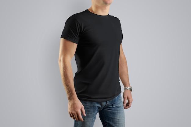 灰色の壁にポーズをとっている若い男の黒い綿のtシャツ。