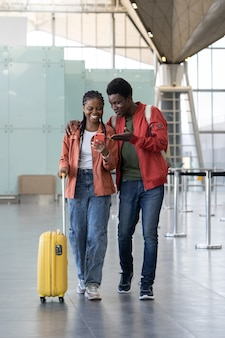 Black couple after plane arrival walk with luggage in airport reading funny messages on smartphone