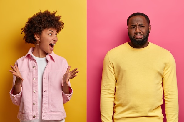 Black couple arguing. annoyed curly haired woman gestures angrily, displeased man made bad mistake, feels sorry, cries from despair, listens wifes quarreling with guilty expression. relationship