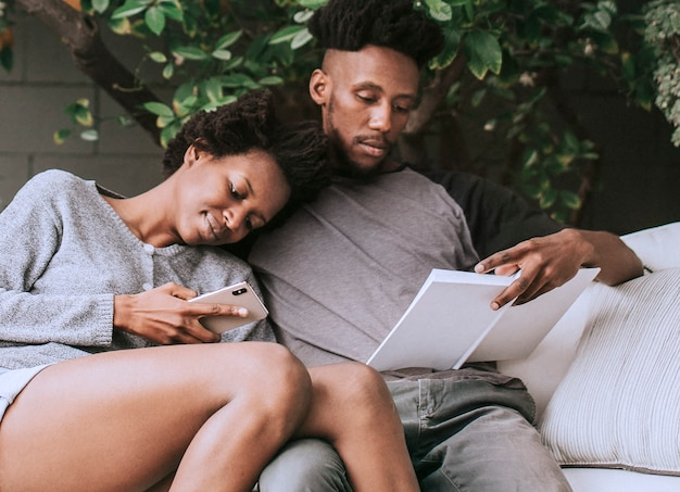 Черная пара читает и играет по телефону в саду