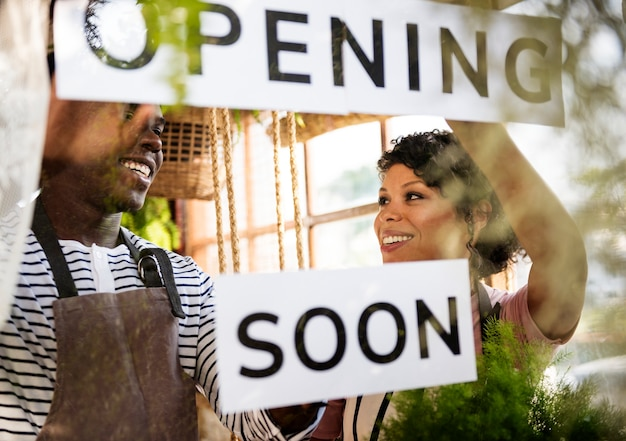 Black couple showing opening soon paper sign