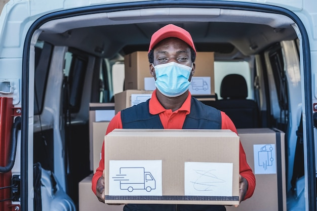 安全マスクを身に着けている貨物トラックの前に荷物を配達する黒い宅配便の男-顔に焦点を当てる