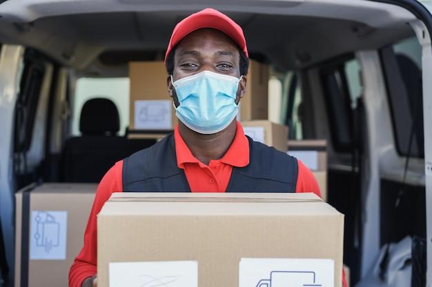 Черный курьер доставляет посылку перед грузовым автомобилем в маске безопасности - фокус на лице