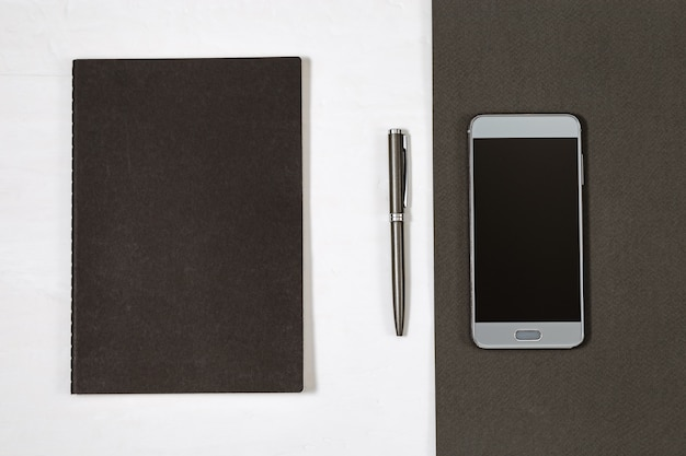 Black cover of closed notebook and silver pen. top view