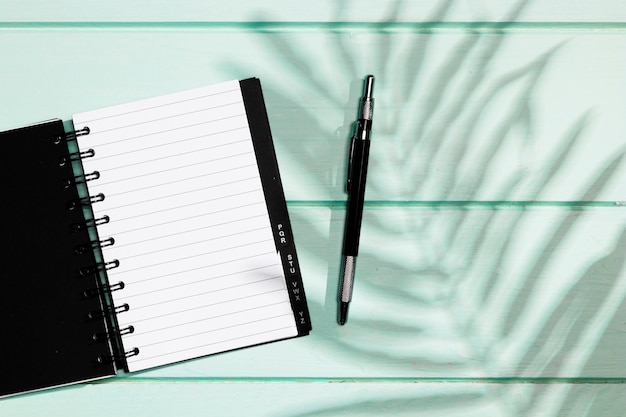 Black cover of notebook with pen and leaves shadow