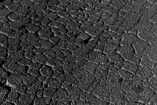 Черная потрескавшаяся текстура alphalt или фон