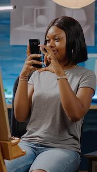 アートデッサンの写真のためのスマートフォンを保持している黒人の創造的な人