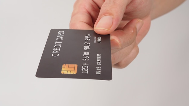 Black credit card in hand isolated on white background.