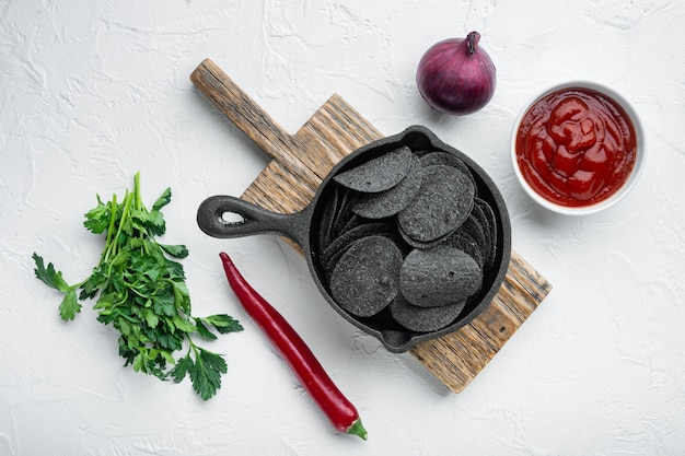 Black crispy potato chips set, with dipping sauces tomato dip sour cream, in cast iron frying pan, on white stone surface, top view flat lay