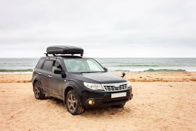 夏の砂浜でトランクボックスと黒のクロスオーバー