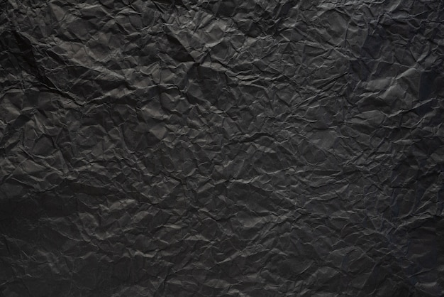 Black crumpled paper texture background.