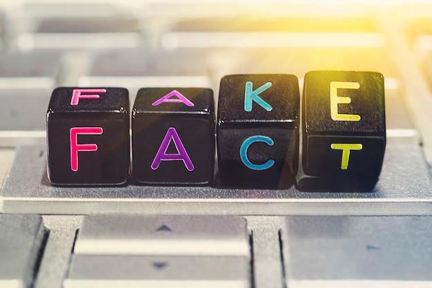 黒い立方体は、灰色のラップトップキーボードで表現を偽物から事実に変更します。事実改ざんの概念。インターネット上の虚偽のニュース。フェイクニュース