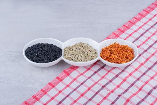 Cumino nero, semi di anice e zafferano in piattini bianchi. foto di alta qualità